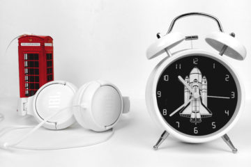Budzik, słuchawki i czerwona budka na białym tle